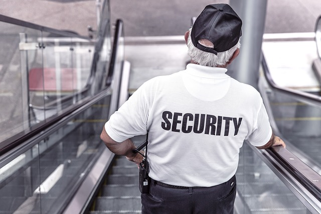 "A photograph of a man in a uniform with the word ""SECURITY"" printed on the pack of his shirt"